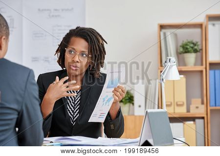 African-American business woman explaining results of her work to colleague