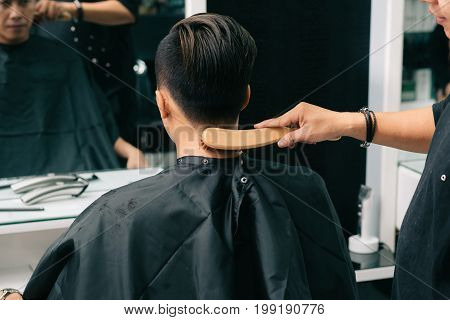 Barber brushing off excess hair from the neck of male client