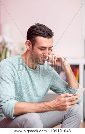 Closeup portrait of smiling young attractive man sitting, holding smartphone and reading from its screen with blurred apartment interior in background
