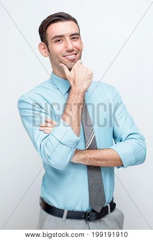 Closeup portrait of smiling young handsome business man looking at camera and touching chin. Isolated view on grey background.
