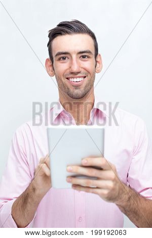 Closeup portrait of smiling young handsome man looking at camera, holding tablet computer and using it. Isolated front view on grey background.