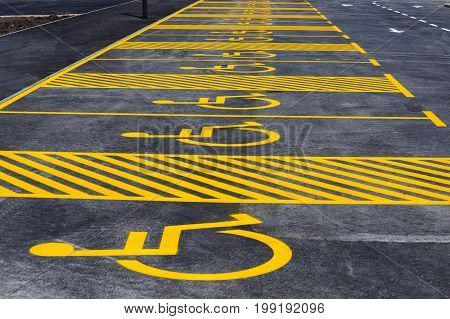 Parking Lot With Painted Yellow Sign Of Wheelchair