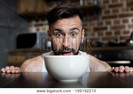 Close-up View Of Hungry Bearded Young Man Looking At Breakfast On Kitchen Table