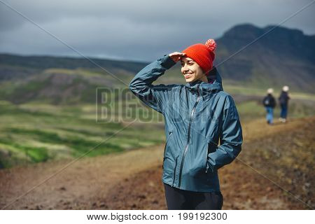 Girl in warm clothing gesturing and observing surroundings on background of mountains of Iceland.