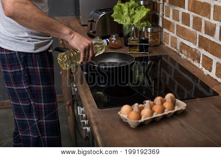 Partial View Of Young Man Preparing Omelet For Breakfast In Kitchen At Home