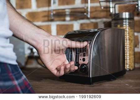 cropped shot of man turning on toaster while preparing toasts at morning