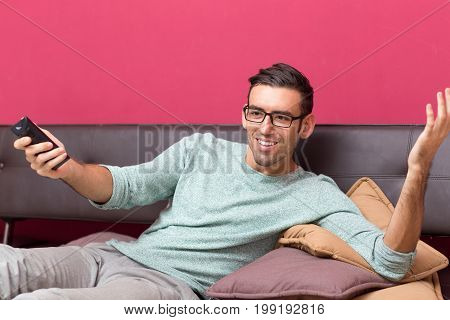 Closeup portrait of smiling young handsome man lying on sofa, watching TV and using remote control at home