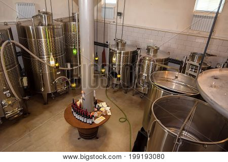 Interior of modern winery with metal vats and wine bottles