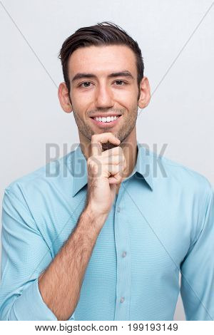 Closeup portrait of smiling young handsome man looking at camera and touching chin. Isolated front view on grey background.