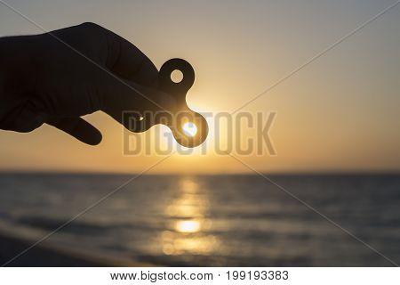 Siluete Of Hand Holding Fidget Spinner