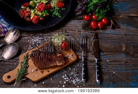 Overhead View Of Colorful Vegetables, Savory Sauces And Salt Served With Grilled Steak On A Rustic W