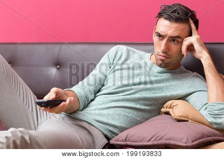 Closeup portrait of tensed young handsome man lying on sofa, watching TV and using remote control at home