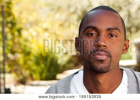 Young African American man looking sad sitting outside.