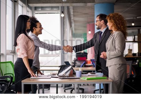 Multiethnic business teams at meeting room shaking hands. Handshake of two men.