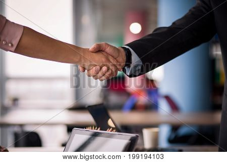 Business partners handshaking. Close up view of woman and man shaking hands.