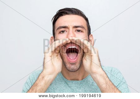 Closeup portrait of serious young man looking at camera, opening mouth widely, cupping hands around mouth and shouting loud. Isolated front view on grey background.