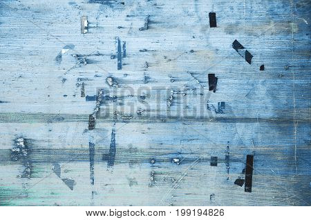 Old bulletin board in blue color. Billboard with torn peeled poster. Plywood panel with worn advertising message. Grunge urban background street outdoor texture.