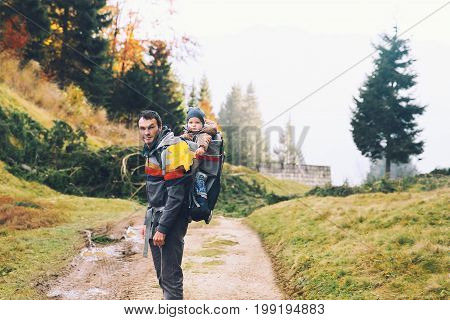 Father hiking with child in carrier backpack on a nature in autumn forest. Valley Bohinj Slovenia Triglav National Park. Family on trekking day in the mountains. Travel Lifestyle Concept.