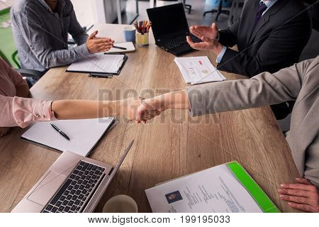Business agreement, handshake of partners after concluding a deal. Two business teams sitting at both sides of table in meeting room.