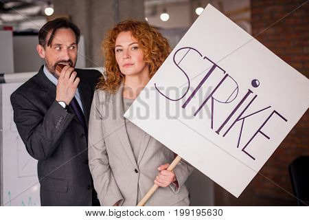 Businesswoman holding big poster with word strike. Red haired fwmale showing unhappy emotions, happy man standing close to her eating cake.