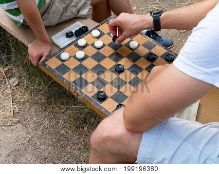 Two people playing checkers outside. Close-up on checkers board