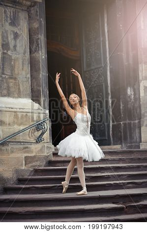 Gorgeous female ballet dancer performing outdoors dancing near and old building.