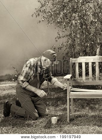 Old Man Painting Bench In Garden