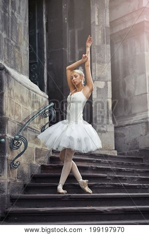 Full length shot of a beautiful young female ballet dancer posing gracefully on the stairway of an old building in the city.