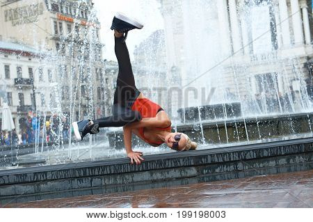 Cool female hip-hop dancer making a handstand while dancing near the fountain at the city center performing outdoors.