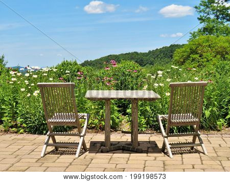 Table and chairs overlooking the mountains and a garden of Summer flowers