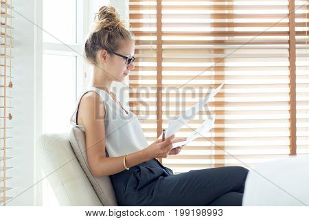 Portrait of serious young Caucasian businesswoman wearing glasses sitting in armchair and working with papers in office