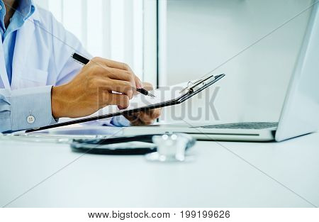 Stethoscope With Clipboard And Laptop On Desk, Doctor Working In Hospital Writing A Prescription, He
