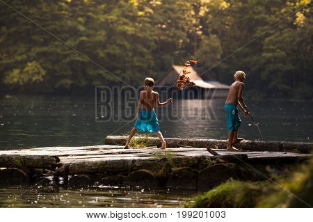 Boys Playing On Dock On Lake