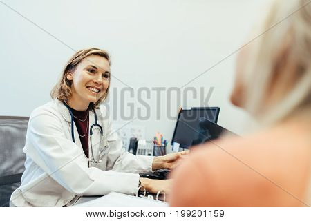 Female doctor listening to her patient during consultation in the office. Medicine professional sitting at her desk and counselling with patient.