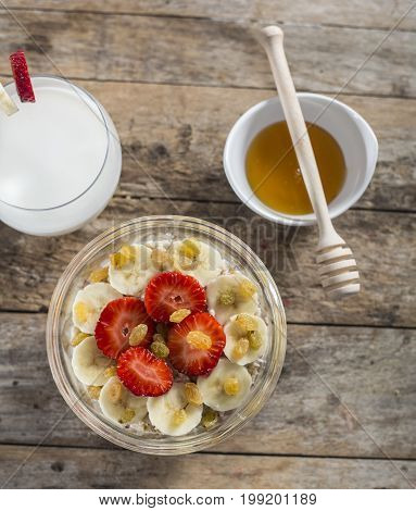 oatmeal porridge with strawberry and banana in wood bowl