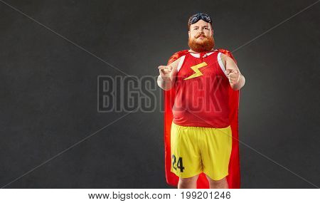 A fat funny man in a superhero costume points a hand at you.