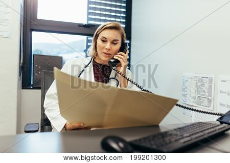 Doctor reading medical records and talking on telephone. Medicine practitioner examining medical reports and using telephone in her clinic.