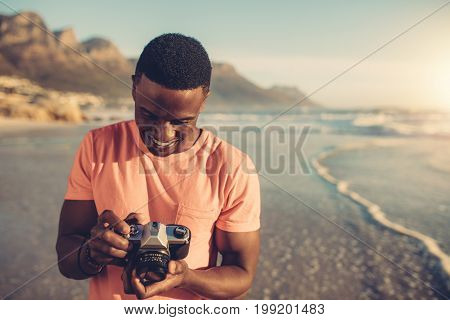 African man checking photos in his digital camera. Young man with digital photo camera standing on the beach.