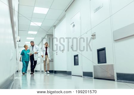 Full length shot of medical team walking down hallway at the hospital. Doctors with nurse walking in hospital corridor and discussing.