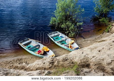 Two Old Blue Boatslife Jackets On A Sandy Beach With Trees