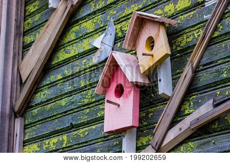 Birdhouse On An Old Wooden House Painted In Different Colours