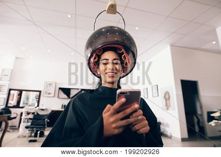 Woman at the spa with rollers to her hair and a steaming machine around the head. Smiling woman looking at the mobile phone at the beauty parlor while undergoing hair steaming.