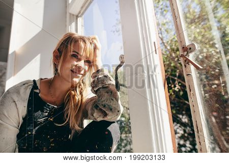 Pensive Female Artist Dirty Sitting And Looking Out Of Window