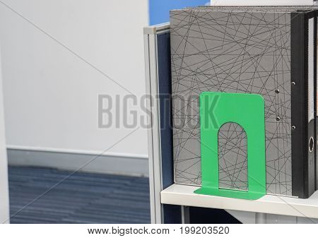 business documents folder with green book end on office desk