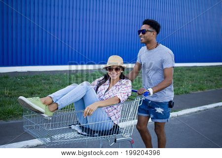 Happy young couple riding on trolley  on empty mall parking , hipster friend have good time during shopping, couple in love riding on shopping cart