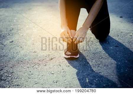 Young girl asian knelt down to do up his shoelaces on street after running exercise Close up Shoe sport and leg