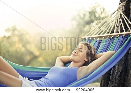 Blonde girl lying in a hammock