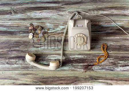 Old coins, antique phone and beads on a wooden table close-up