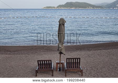 Two sunbeds and closed umbrella with small table on the empty beach