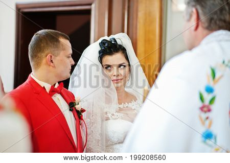 Wedding Couple Standing In The Church In The Presence Of Priest During Their Wedding Ceremony.